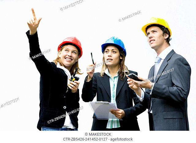 Team of young professionals on a construction site wearing hard hat and using electronic device