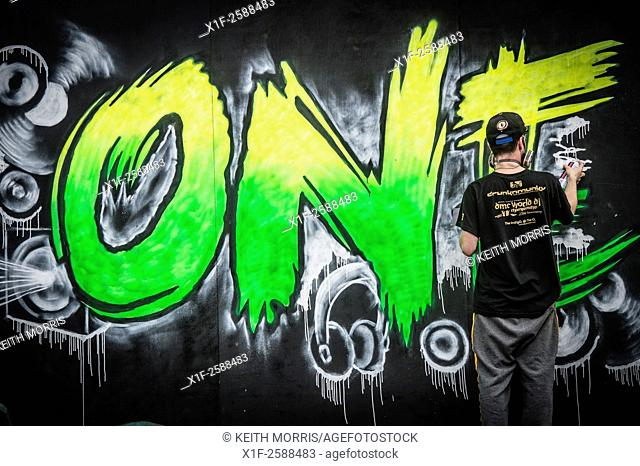 A rear view of a young teenage man spray painting street art - the word 'One' on a wooden hoarding wall UK