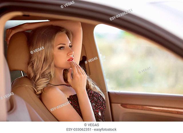 Beautiful young girl touching lips in luxury car, woman driver smarten oneself up