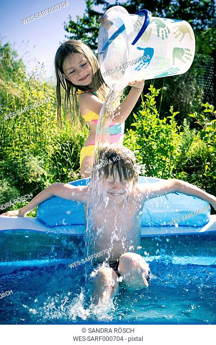 Girl splashing water on brother in inflatable pool