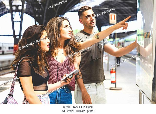 Friends with cell phone on train station platform looking at departures board