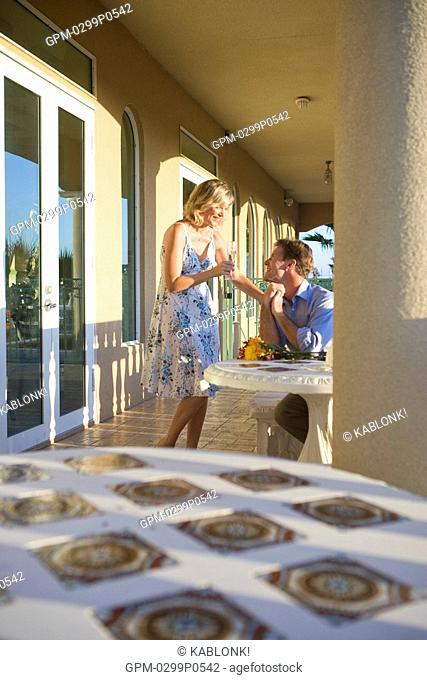 Young happy couple smiling with champagne on balcony