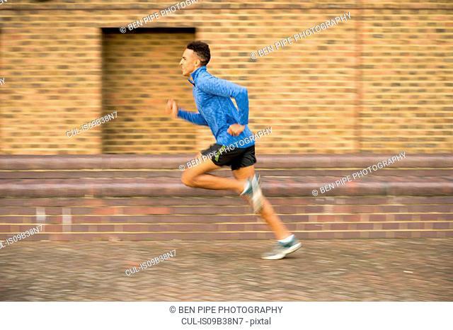 Man running past brick wall, Wapping, London, UK