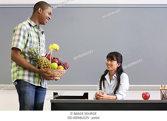 Male high school student giving teacher a basket of fruit