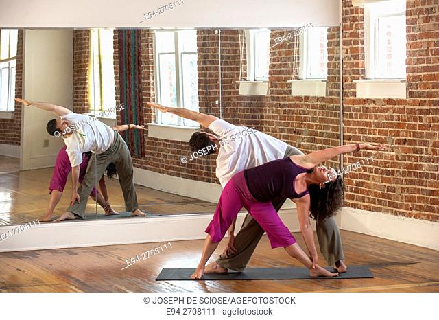 A 43 year old woman and yoga expert doing yoga poses with male companion