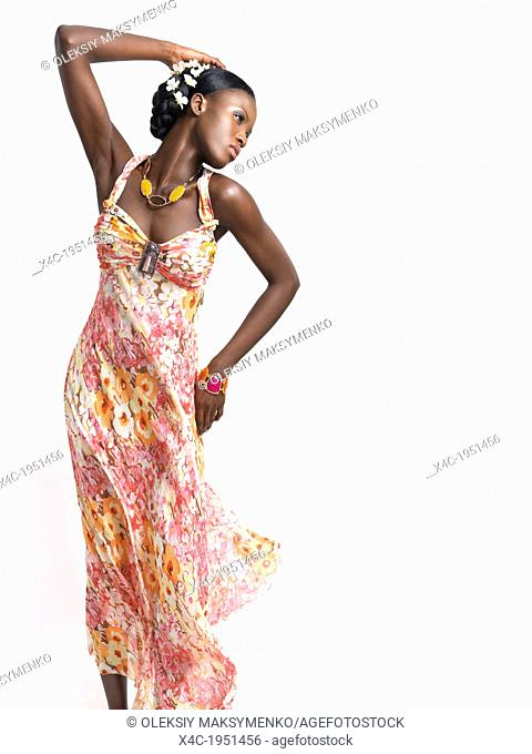 Beautiful young african american woman wearing a flying pink floral summer dress isolated on white background