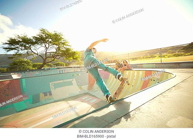 Friends watching man perform skateboard trick at skate park