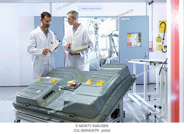 Scientists inspecting lithium ion car battery components in battery research facility
