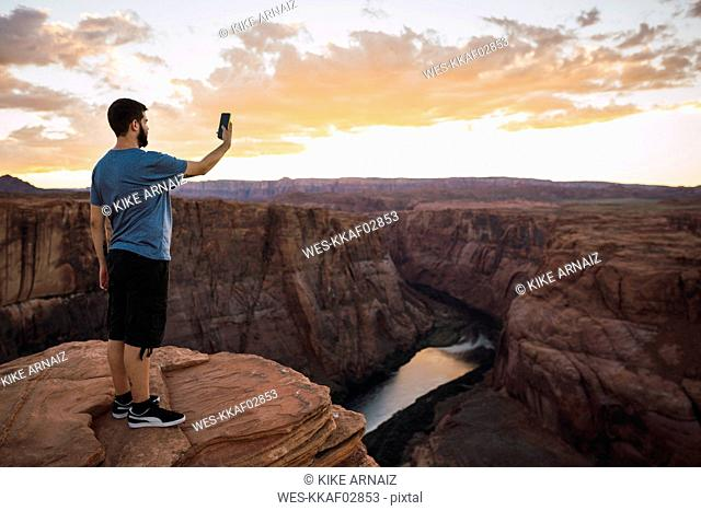 USA, Arizona, Colorado River, Horseshoe Bend, young man on viewpoint using smartphone, photographing