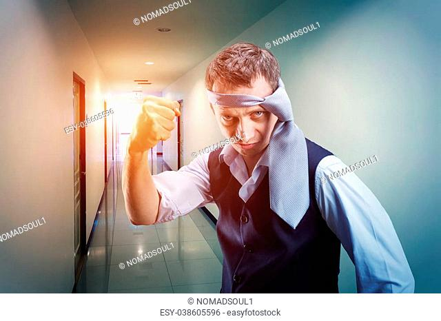 Fighting businessman with a tie on his head in the office