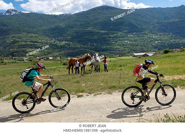 France, Hautes Alpes, Guillestre, children on mountain bike