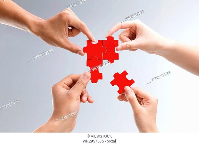 The hand holding the puzzle