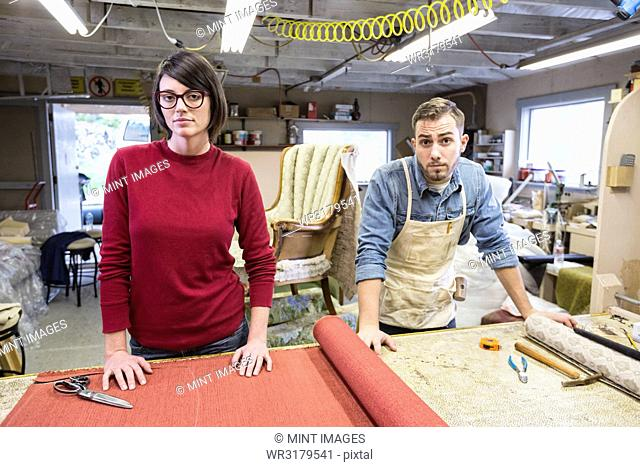 A young Caucasian couple working on a chair as a team of upholsterers