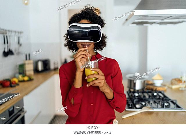 Woman standing in her kitchen, wearing VR goggles, drinking orange juice