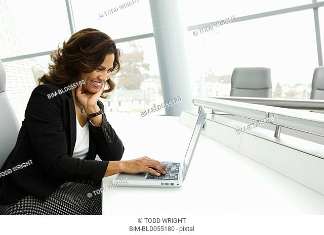 Hispanic businesswoman typing on laptop