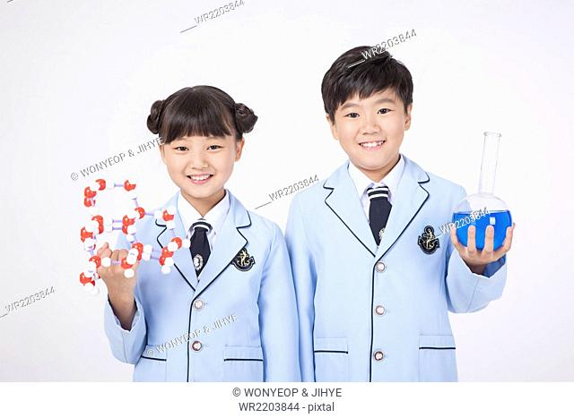 Elementary school age girl holding molecular structure and a boy next to her holding a round bottom flask with blue liquid in it