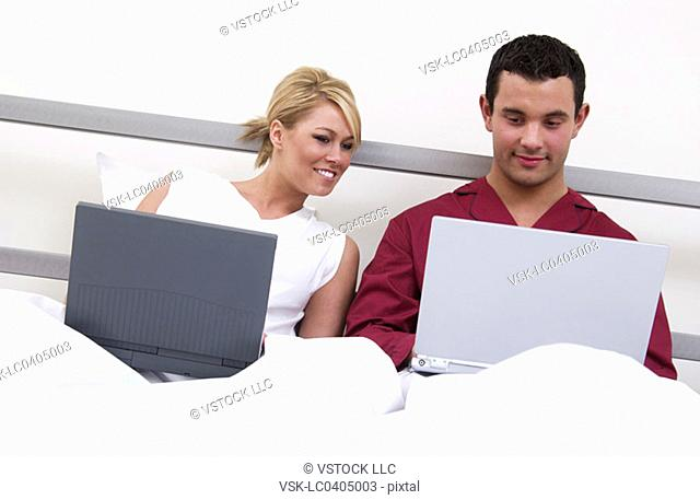 Couple in bed working on laptop computers