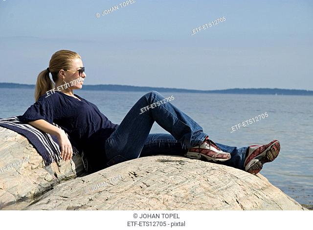 A young woman sitting by the sea Sweden