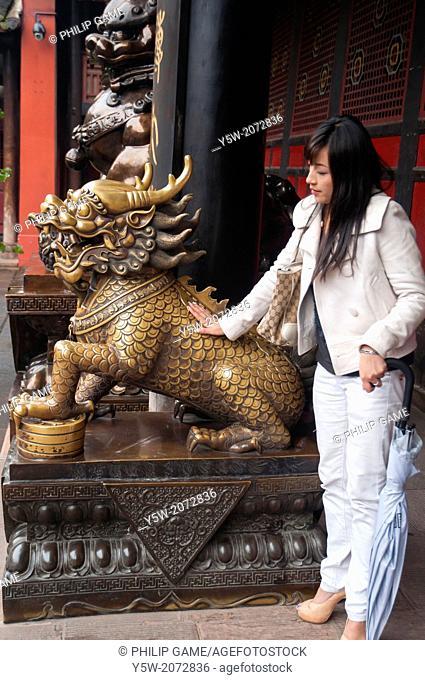 Young woman patting a guardian lion at the Wenhou Monastery at Chengdu, Sichuan, China