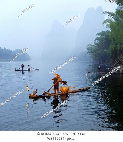 Cormorant fishermen in mist at dawn on the Li river with Karst mountain peaks near Xingping China