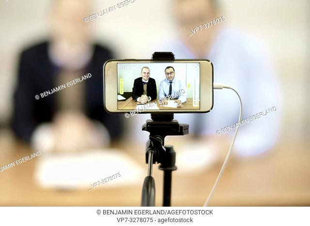 phone recording live stream video of business men at online conference in office, in Cottbus, Brandenburg, Germany