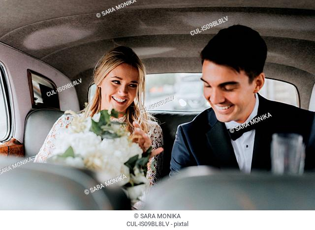 Bride and bridegroom in backseat of car