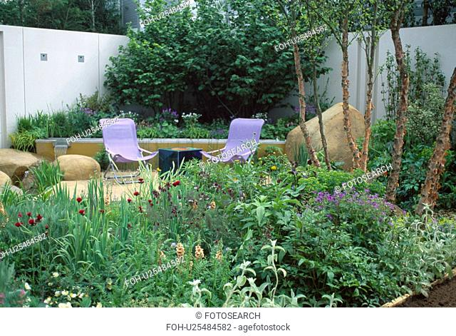 Modern mauve chairs on patio in town garden with summer borders and white walls