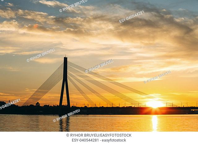 Riga, Latvia. Scenic View Of Vansu Cable-Stayed Bridge Over The Daugava River, Western Dvina In Bright Sunset Or Sunrise Time