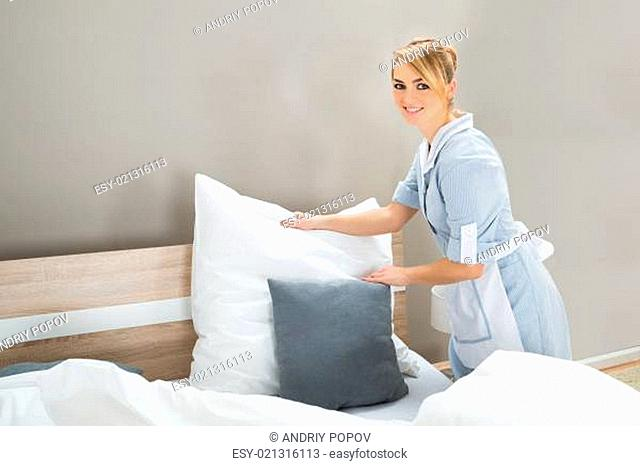 Young Female Happy Housekeeping Worker Arranging Pillows In Bedroom