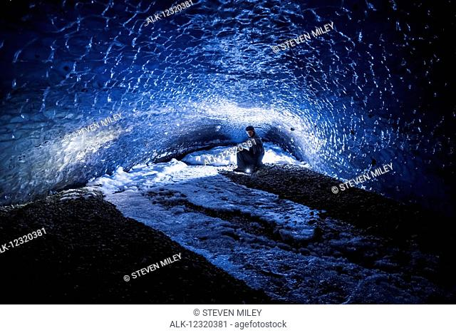 A man illuminates the end of a dark, lengthy tunnel within the ice of Canwell Glacier in the Alaska Range