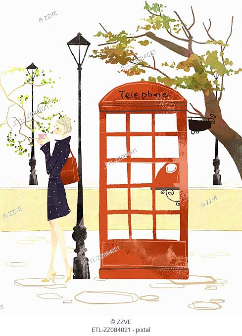 Woman standing near telephone booth holding takeaway coffee