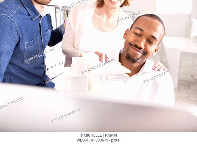 Smiling man presenting architectural model at video conference