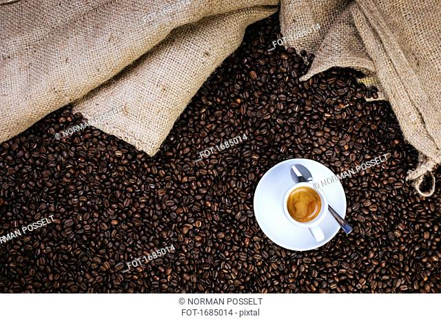 Directly above shot of espresso cup on roasted coffee beans