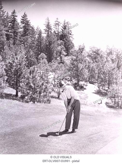 Man smoking pipe while playing golf (OLVI007-OU991-F)