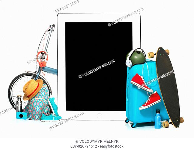 The blue suitcase, sneakers, clothing, hat, and laptop on white background. The travel, tourism and holidays concept. Collage