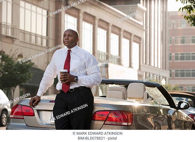 Black businessman drinking coffee near convertible