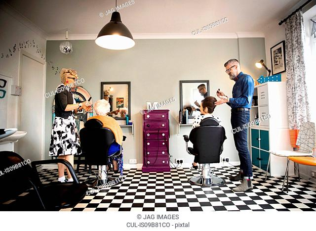 Couple in vintage clothes working on customers in quirky hair salon