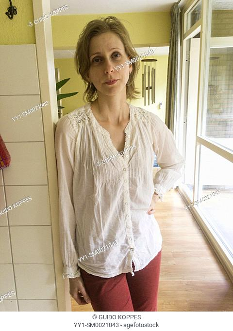 Tilburg, Netherlands. Adult caucasian woman leaning against a residential kitchen doorpost