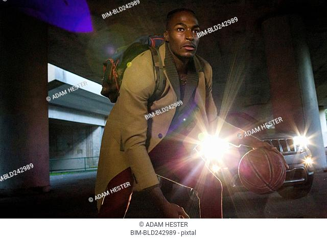 Headlights shining on Black man wearing backpack playing basketball