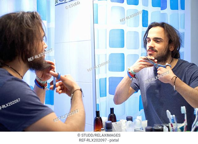 Young man cutting beard in front of mirror in bathroom