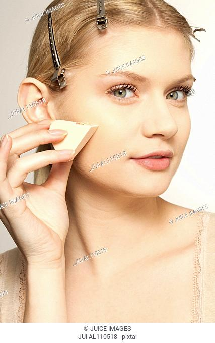 Portrait of young woman using skin care product