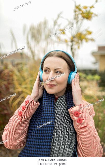 Smiling woman listening to music with headphones outside