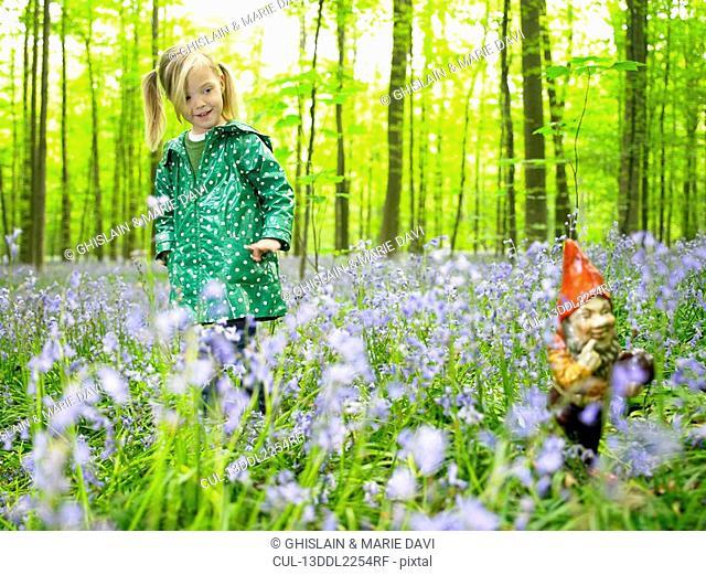 Girl looking at a garden gnome