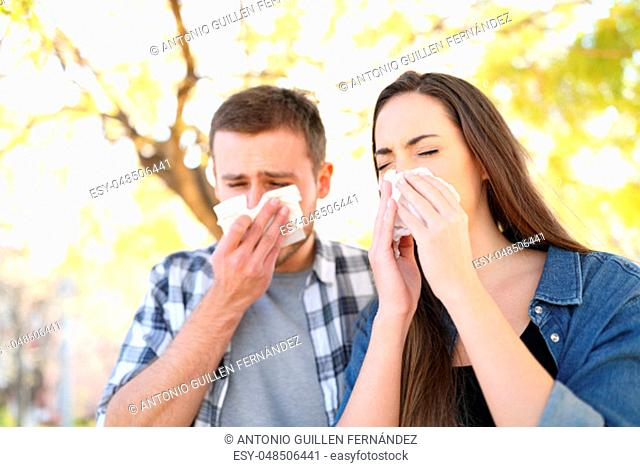 Sick couple sneezing together covering mouth with wipes in a park