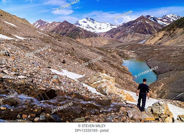 A hiker gazes over the 'intersection' of three branches of Castner Glacier at Mount Silvertip rising in the distance in the Alaska Range; Alaska