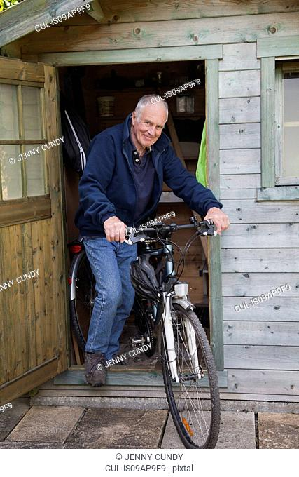 Senior man on bike by shed