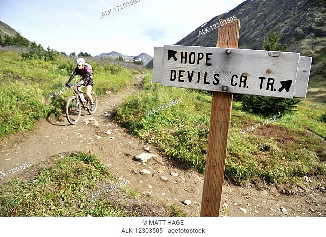 Woman rides a full suspension mountain bike on the Devils Pass Trail in the Chugach National Forest, Kenai Peninsula, Southcentral Alaska