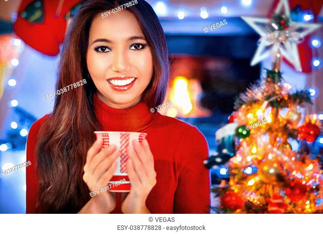 Christmas, x-mas, winter, happiness concept. Attractive smiling woman with cap near fireplace over holiday lights background