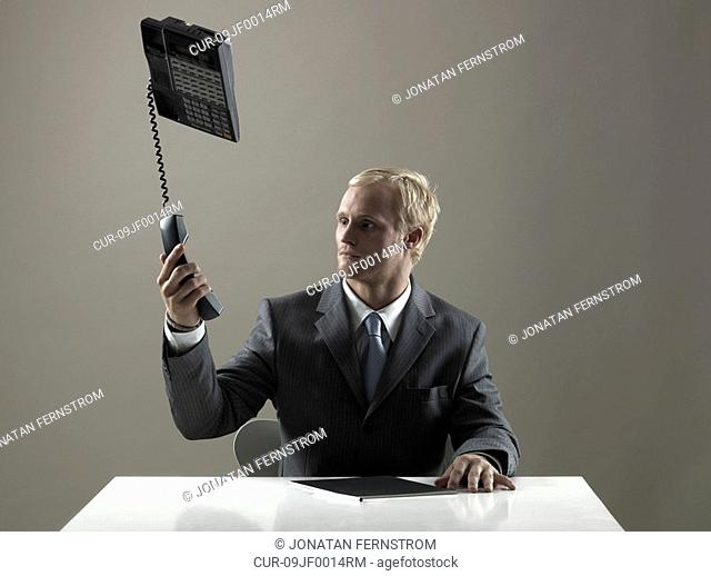 Business man holding phone in mid-air