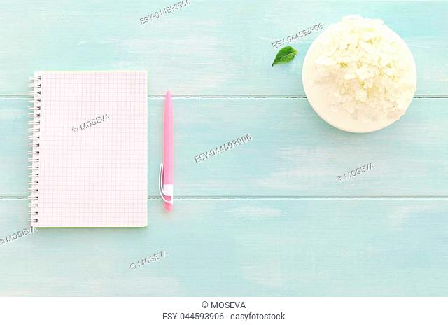 Open notebook with pink pen, coffee cup and hydrangea on mint wooden background. Copy space background, top view flat lay overhead
